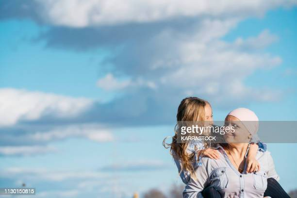 a woman with cancer is next to her daughter. a girl is hugging a woman happy - beautiful women breast stock pictures, royalty-free photos & images