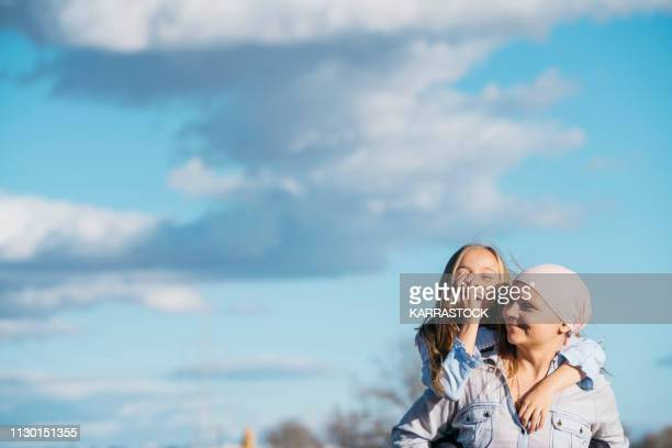 a woman with cancer is next to her daughter. a girl is hugging a woman happy - cancer illness stock pictures, royalty-free photos & images
