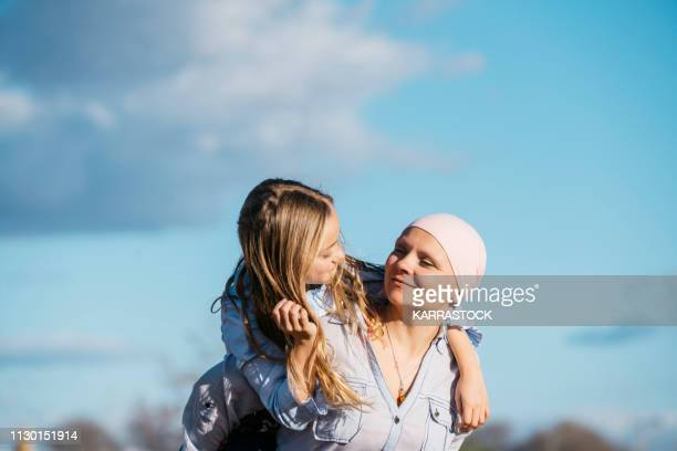 a woman with cancer is next to her daughter. a girl is hugging a woman happy - busen stock-fotos und bilder
