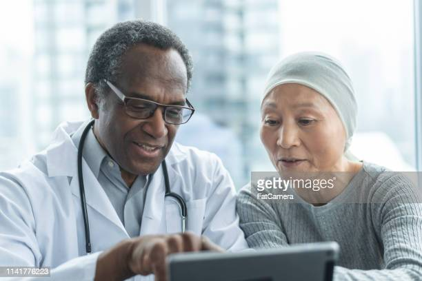 woman with cancer reviews test results with doctor - chemotherapy stock pictures, royalty-free photos & images