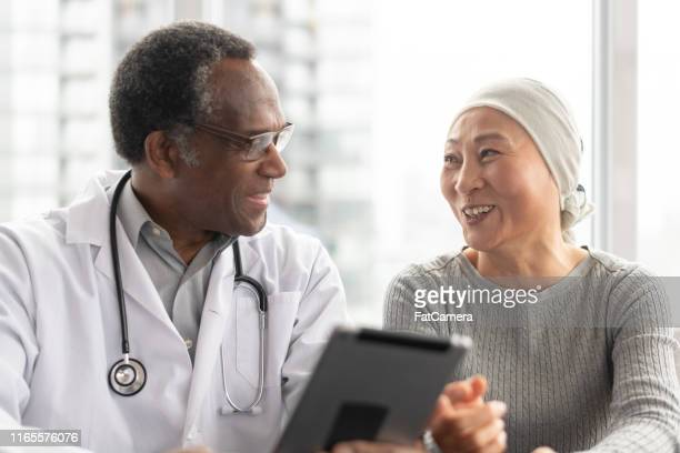 woman with cancer reviews test results with doctor - oncology stock pictures, royalty-free photos & images