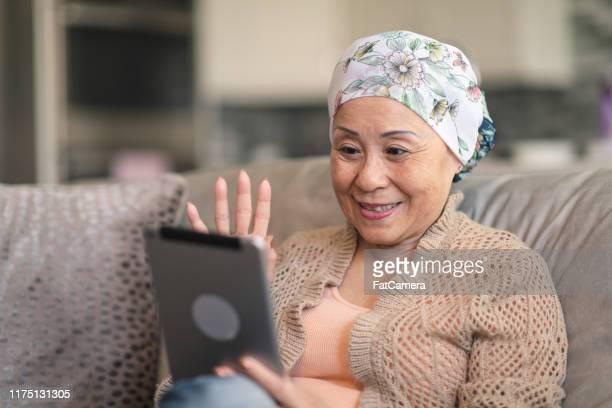 デジタルタブレット上の友人と癌ビデオチャットを持つ女性 - chinese ethnicity ストックフォトと画像