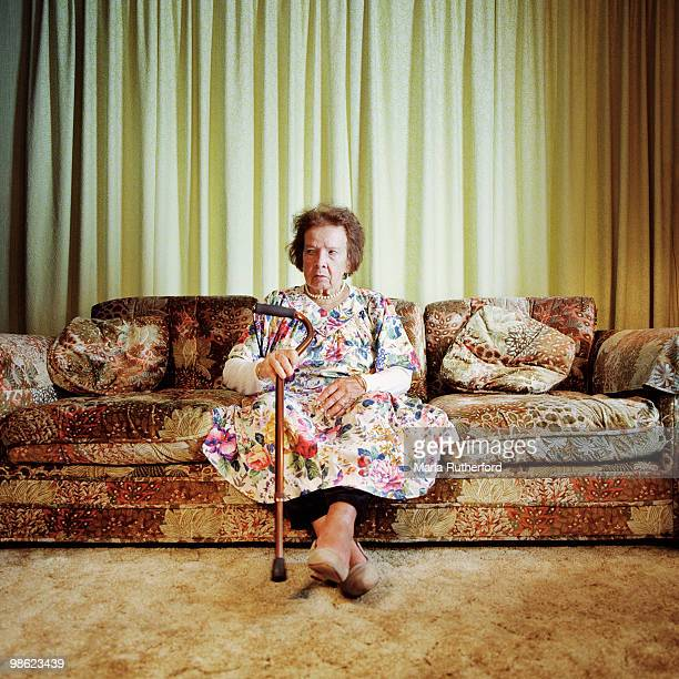 Woman with cane seated on sofa