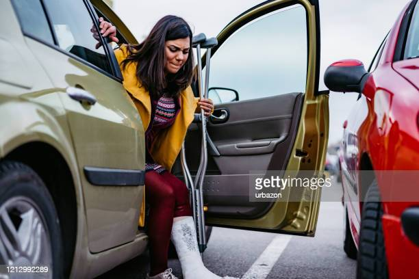 woman with cast getting out of car - injured stock pictures, royalty-free photos & images