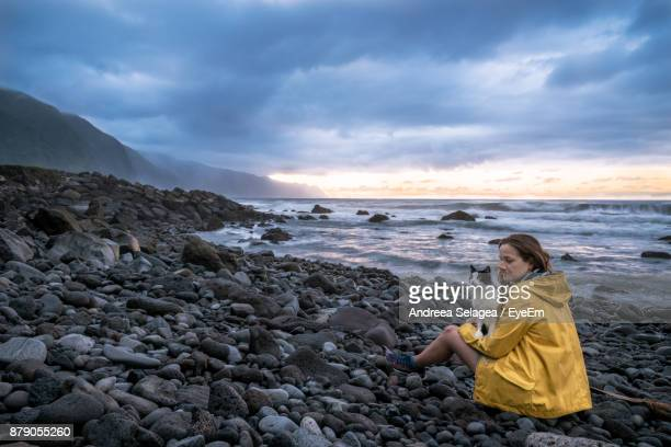 Woman With Cat Sitting At Beach Against Sky