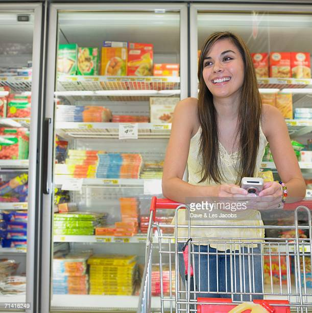 Woman with cell phone at supermarket