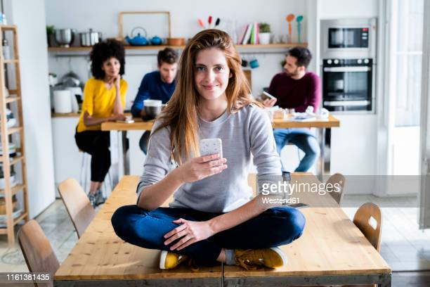 woman with cell phone sitting on dining table at home with friends in background - quatro pessoas imagens e fotografias de stock