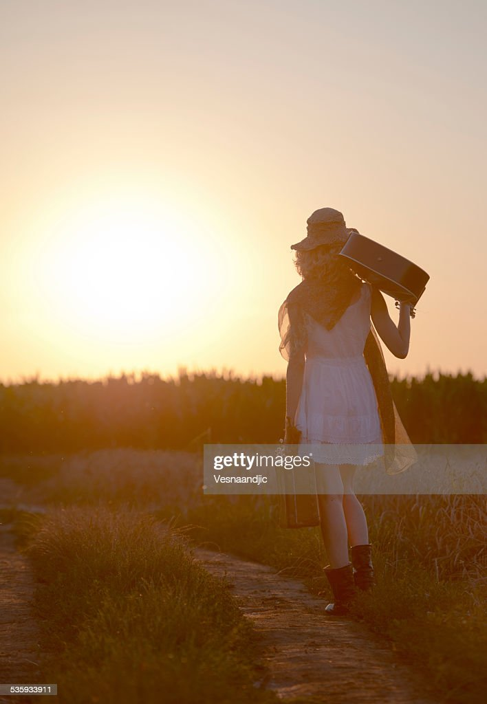 Woman with cello and suitcase in sunset : Stock Photo