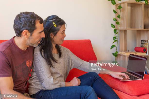woman with cerebral palsy and her partner doing home finances - david freund stock pictures, royalty-free photos & images