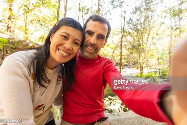 woman with cerebral palsy and her partner taking a selfie - david freund stock pictures, royalty-free photos & images