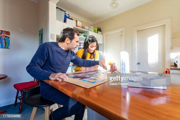 woman with cerebral palsy doing a puzzle at home - david freund stock pictures, royalty-free photos & images