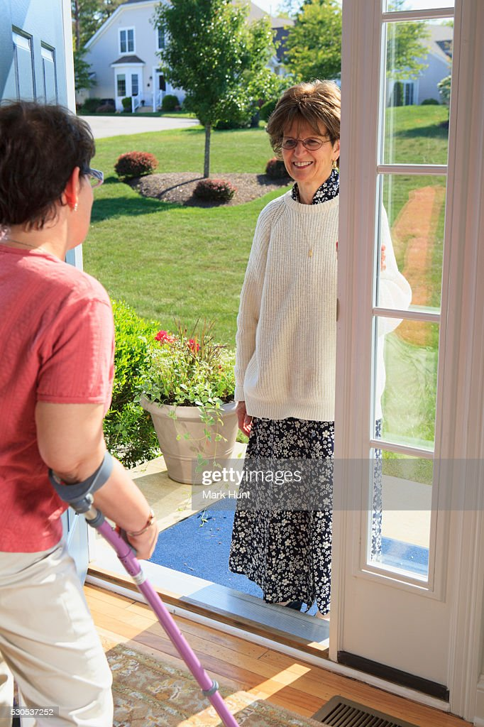 Woman with cerebral palsy greeting someone at the door of her home woman with cerebral palsy greeting someone at the door of her home stock photo m4hsunfo