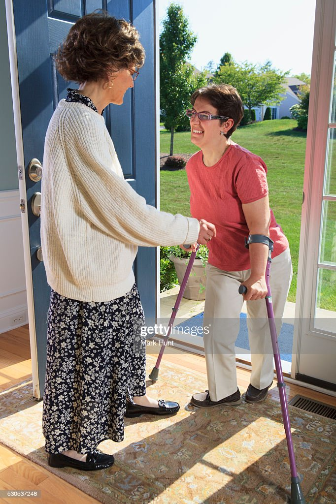Woman with cerebral palsy greeting someone at the door stock photo woman with cerebral palsy greeting someone at the door stock photo m4hsunfo