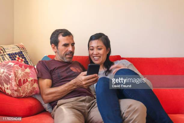 woman with cerebral palsy looking at a phone with her partner - david freund stock pictures, royalty-free photos & images