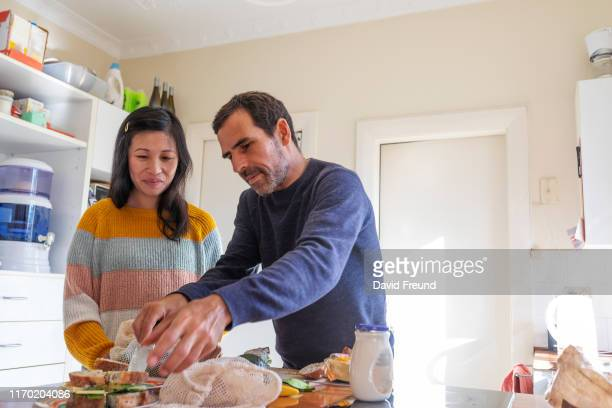 woman with cerebral palsy making lunch with her partner - david freund stock pictures, royalty-free photos & images