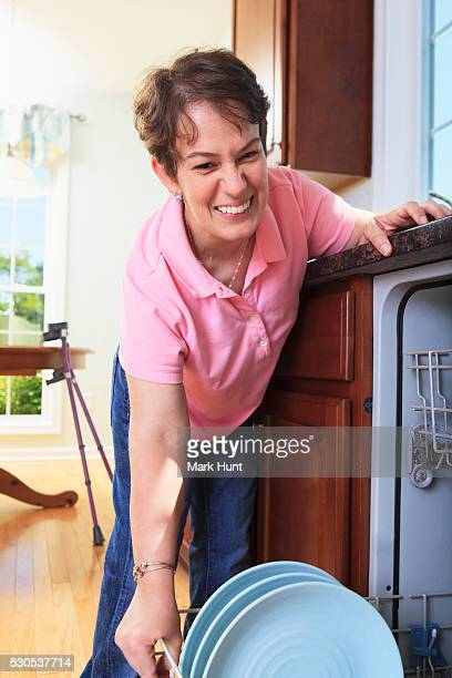 Woman with cerebral palsy putting dishes in a dishwasher