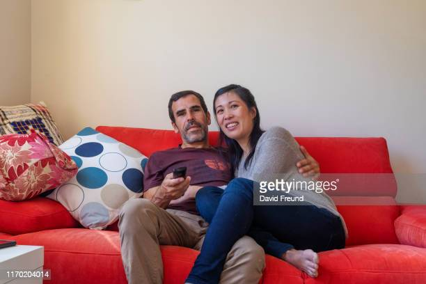 woman with cerebral palsy watching tv with her partner - david freund stock pictures, royalty-free photos & images