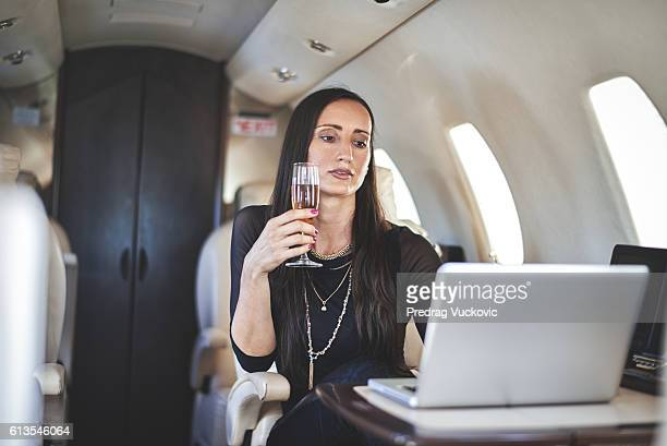 Woman with champagne in private aeroplane