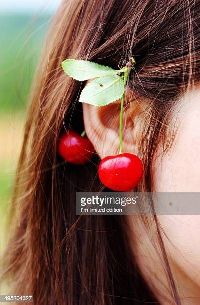 Woman with cherries on her ear