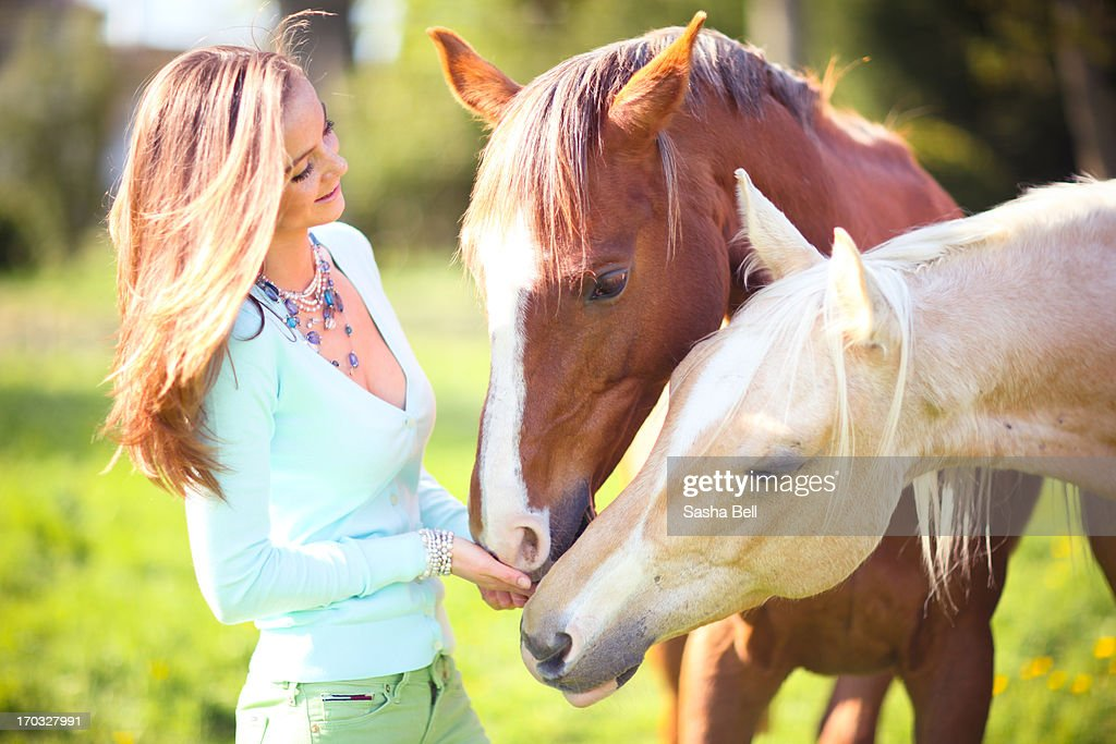 Woman with chestnut and Palomino horses : Stock Photo