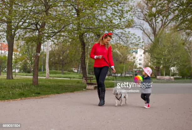 Woman with child and dog walking in park