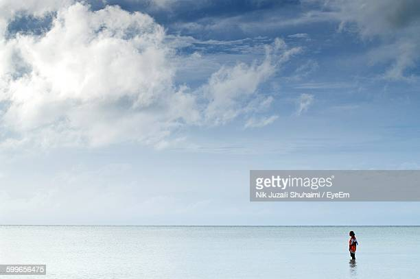 woman with child standing in sea against cloudy sky - unknown gender stock pictures, royalty-free photos & images