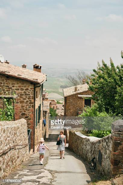 woman with child walking down street with old houses - モンタルチーノ ストックフォトと画像