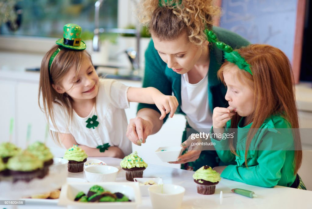 Woman with children decorating cupcakes : Stock Photo