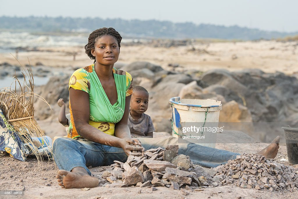 Woman with children is crushing stones for a living : Stock Photo