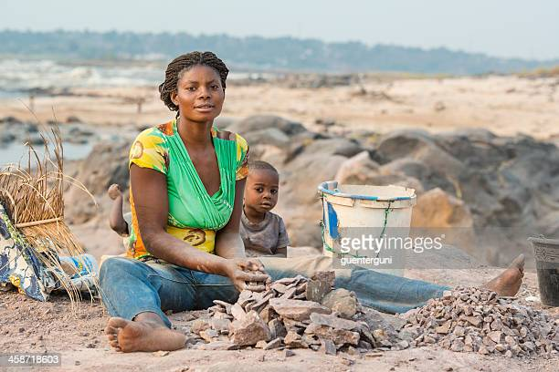 woman with children is crushing stones for a living - democratic republic of the congo stock pictures, royalty-free photos & images