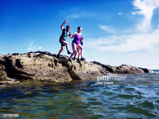 woman with children jumping into the sea - sea swimming stock pictures, royalty-free photos & images