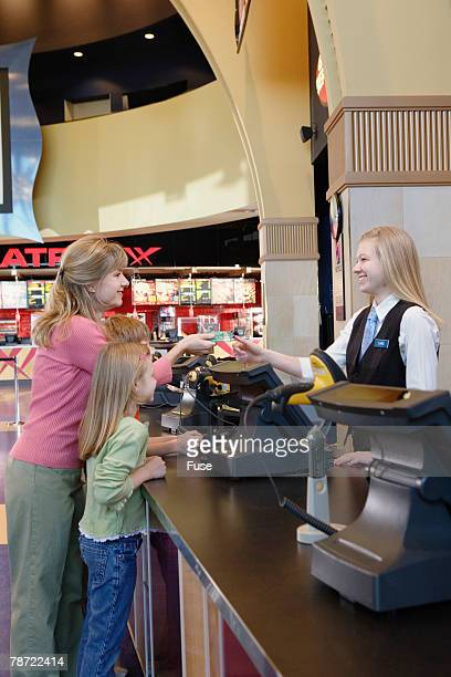 Woman with Children Paying at Ticket Counter in Movie Theater