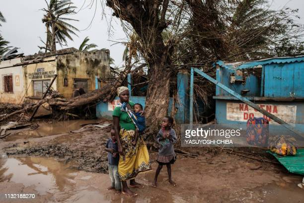 A woman with children stand on a muddy street in Buzi Mozambique on March 23 after the area was hit by the Cyclone Idai The death toll in Mozambique...