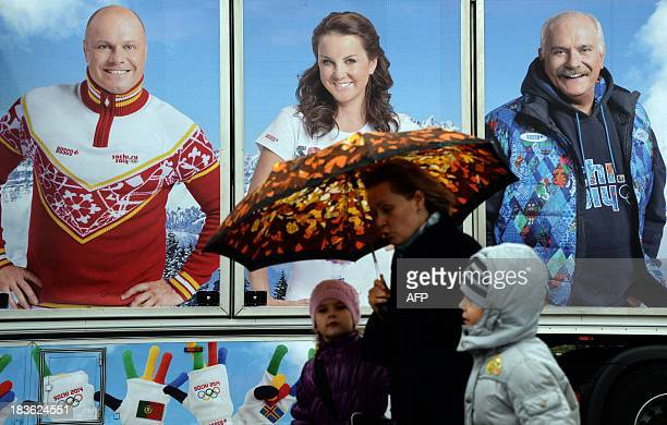 A woman with children walks past a sportswear company shuttle van advertising sports clothing with the Sochi 2014 Winter Olympic logos during the...