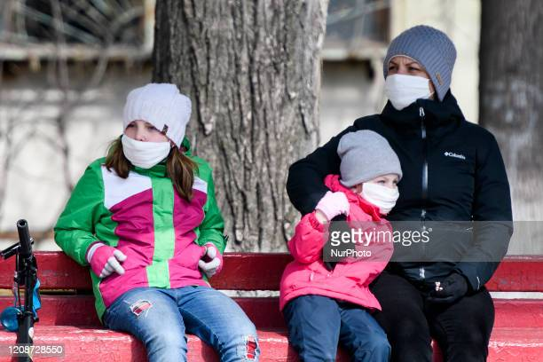 Woman with children wearing protective masks as a preventive measure against the coronavirus COVID-19 on street in Kyiv, Ukraine on March 31, 2020