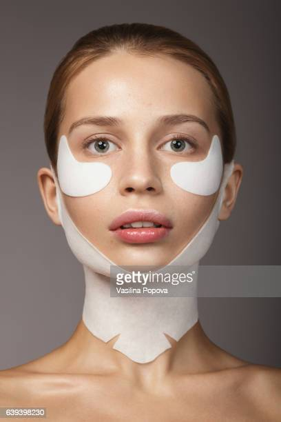 Woman with chin and neck lifting mask and eye patches