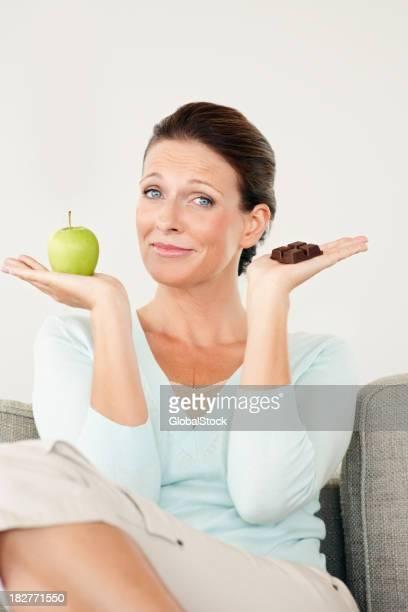 Mulher com chocolate e escolher o que comer maçã