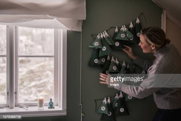 woman with christmas calendar with gifts - advent calendar stock photos and pictures