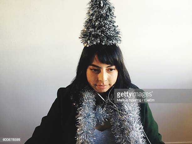 Woman With Christmas Decorations At Home Against Wall