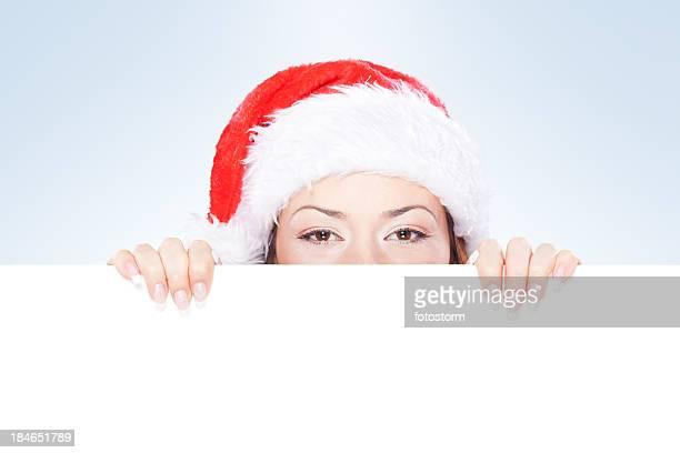 donna con cappello di natale sbirciare dietro vuoto banner - mamma natale foto e immagini stock