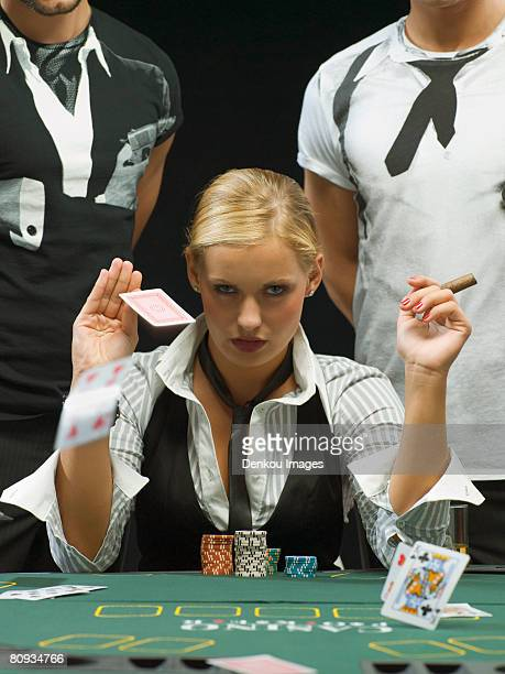 woman with cigar throwing playing cards at poker game - beautiful women smoking cigars stock photos and pictures