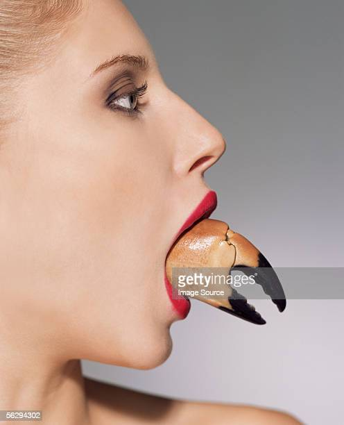 Woman with claw in her mouth
