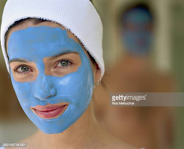 Woman with clay face mask, close-up