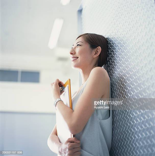 Woman with clipboard leaning against wall, smiling, low angle view