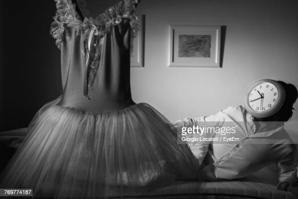 Woman With Clock On Face By Dress In Bedroom