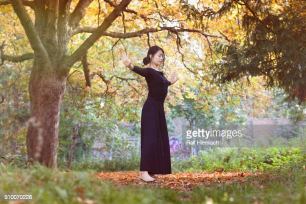 Woman with closed eyes and arms outstretched standing on field against trees at park