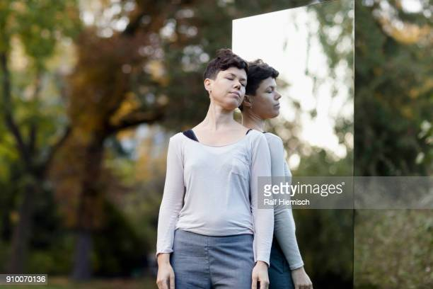 Woman with closed eyes leaning on mirror against trees at park