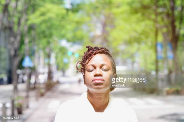 Woman with closed eyes standing outside