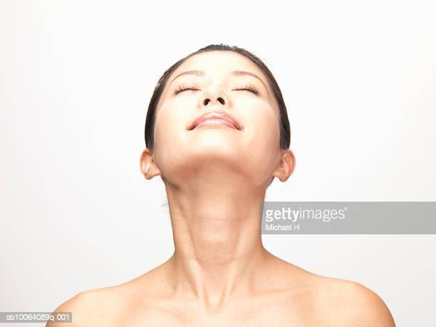 woman with closed eyes tilting head back, studio shot - cabeza hacia atrás fotografías e imágenes de stock