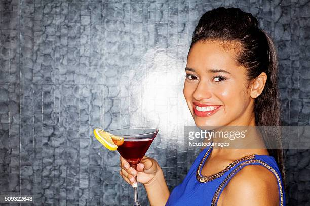 Woman With Cocktail Drink Against Wall In Nightclub